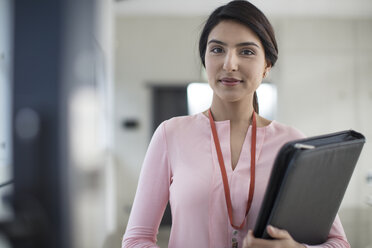 Portrait of young woman holding folder on the corridor in office - ZEF14933