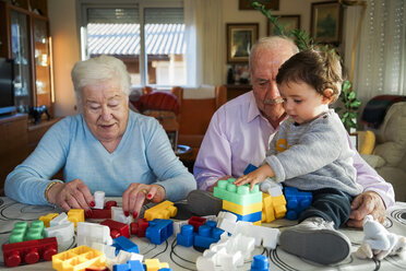 Great-grandparents and baby girl playing together with plastic building bricks at home - GEMF01857
