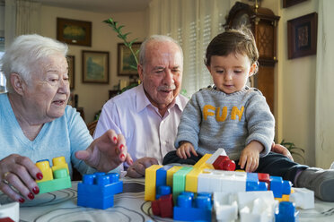 Great-grandparents and baby girl playing together with plastic building bricks at home - GEMF01860