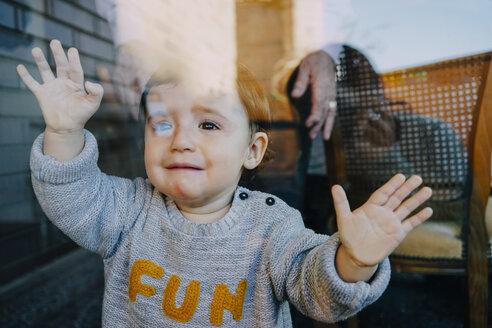 Crying baby girl behind glass door - GEMF01863