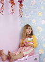Portrait of little girl with red lips sitting barefoot on pink chest of drawers - FSF00990