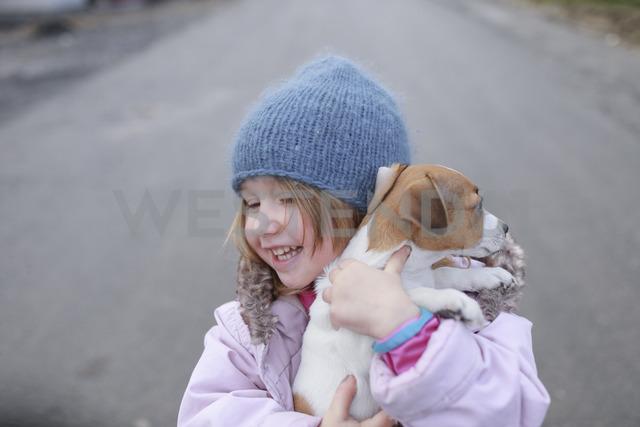 Happy little girl holding Jack Russel Terrier puppy - KMKF00144