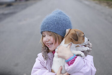 Happy little girl holding Jack Russel Terrier puppy - KMKF00144