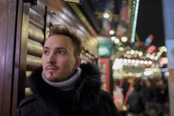 Portrait of young man at Christmas market - KMKF00149