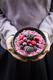 Girl holding bowl with overnight oats mit frozen berries - LVF06641
