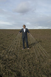 Businessman standing on a field tied to strings - PSTF00061
