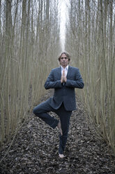 Businessman practicing yoga amidst willows - PSTF00067
