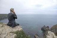UK, Cornwall, Gwithian, businessman sitting at the coast talking on cell phone - PSTF00073