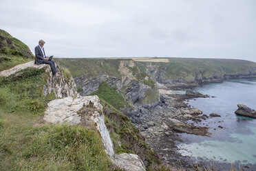UK, Cornwall, Gwithian, businessman sitting at the coast using laptop - PSTF00076