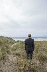 UK, Cornwall, Hayle, businessman standing in beach dunes looking at view - PSTF00079