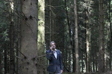 Businessman on cell phone in forest - PSTF00088