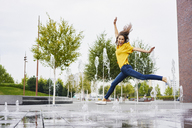Happy young woman jumping in the air - BSZF00206