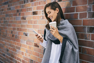 Happy woman with coffee to go looking at cell phone in front of brick wall - BSZF00209