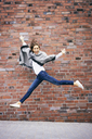 Happy young woman jumping in the air in front of brick wall - BSZF00212