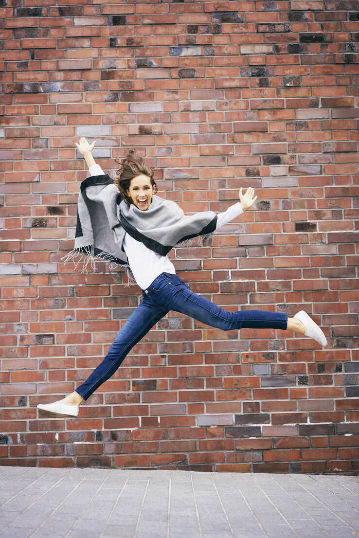 Happy young woman jumping in the air in front of brick wall - BSZF00212 - Bartek Szewczyk/Westend61