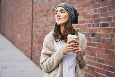 Portrait of daydreaming young woman with coffee to go - BSZF00215
