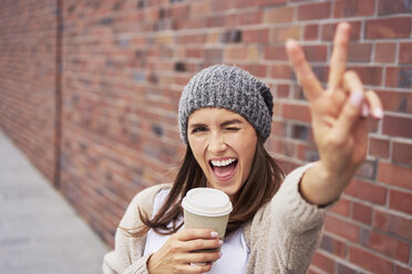 Portrait of young woman with coffee to go showing victory sign - BSZF00218