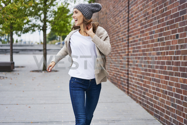 Happy woman running on the street - BSZF00224