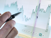 Hand of a stock broker analysing line graph on computer screen - ABRF00070