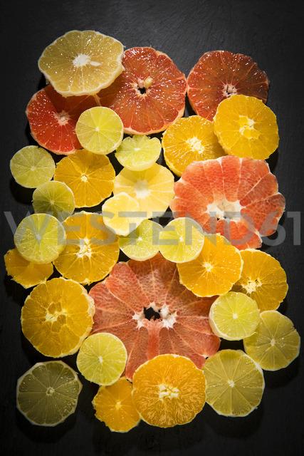 Sliced citrus fruits on black ground - MAEF12515