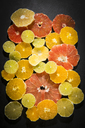 Sliced citrus fruits on black ground - MAEF12515