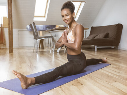 Portrait of smiling young woman in yoga pose doing splits - MADF01379