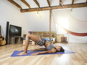 Young woman practicing yoga in attic - MADF01382