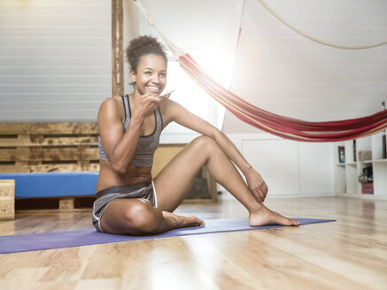 Smiling young woman sitting on yoga mat using cell phone - MADF01385