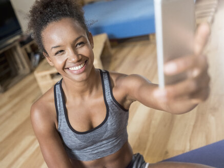 Smiling young woman in sportswear taking a selfie - MADF01388