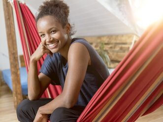 Portrait of happy young woman sitting in hammock - MADF01397