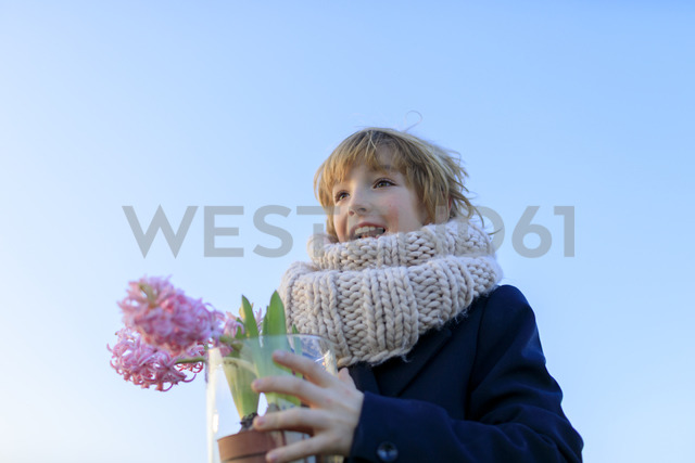 Portrait of happy boy with potted hyacinths against blue sky - KMKF00154