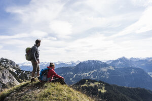 Austria, Tyrol, young couple in mountainscape looking at view - UUF12563