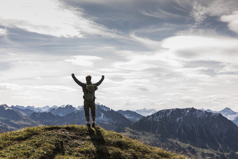 Austria, Tyrol, young man standing in mountainscape cheering - UUF12566