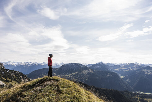 Austria, Tyrol, young woman standing in mountainscape looking at view - UUF12569