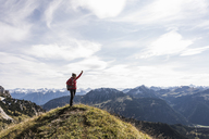 Austria, Tyrol, young woman standing in mountainscape cheering - UUF12572
