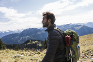 Austria, Tyrol, young man in mountainscape looking at view - UUF12581
