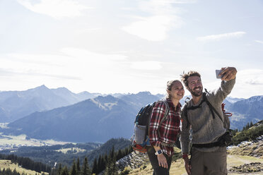 Austria, Tyrol, smiling young couple taking a selfie in mountainscape - UUF12596