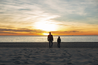 Father and son walking on the beach at sunset - EBSF02016