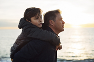 Father carrying son piggyback by the sea - EBSF02022