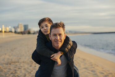 Portrait of father carrying son piggyback on the beach - EBSF02025