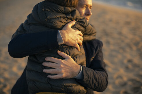 Father hugging son on the beach - EBSF02028