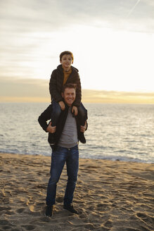 Portrait of father carrying son piggyback on the beach - EBSF02031