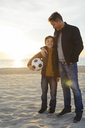 Father embracing son with football on the beach at sunset - EBSF02037