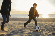 Father and son playing football on the beach at sunset - EBSF02043
