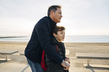 Father and son with scooter on beach promenade at sunset - EBSF02049