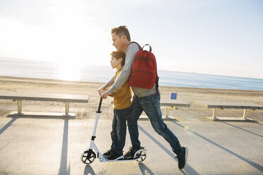 Father and son riding scooter on beach promenade at sunset - EBSF02052
