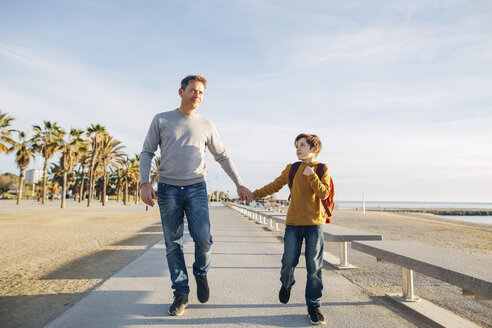 Father and son walking on beach promenade - EBSF02061