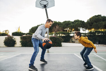 Father and son playing basketball on an outdoor court - EBSF02064