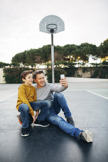 Father and son sitting on basketball outdoor court taking a selfie - EBSF02067