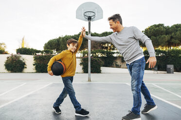 Father and son high fiving on basketball outdoor court - EBSF02070